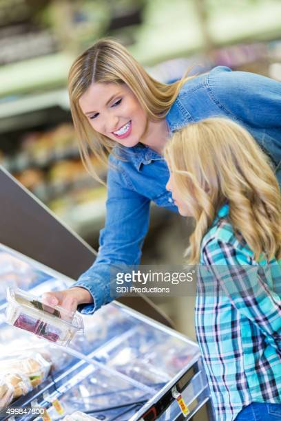 Mother shopping at grocery store deli counter with daughter
