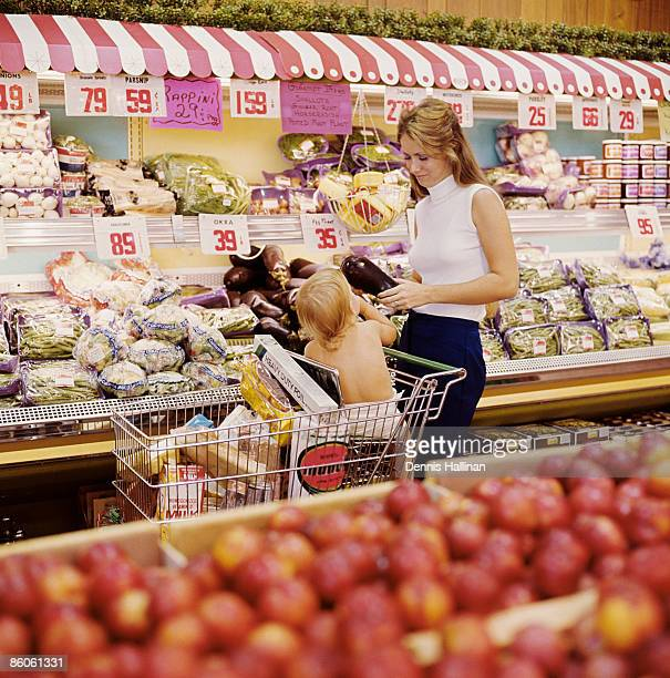 Mother shopping for groceries with baby