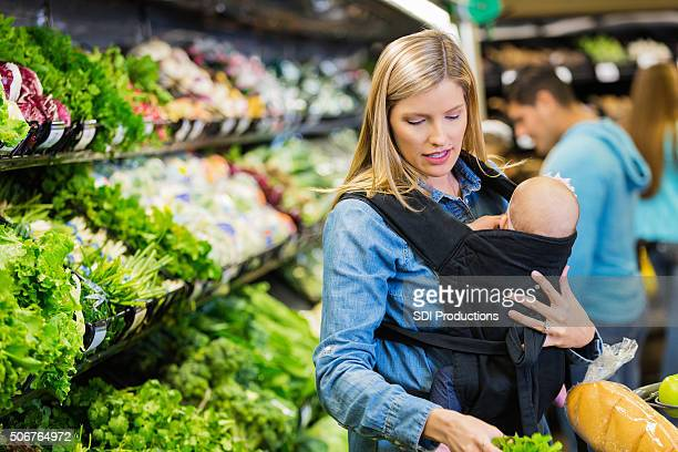 Mother shopping with infant daughter in grocery store or supermarket