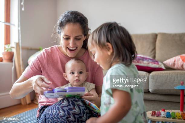 Mother showing a book to a baby and a toddler in the living room