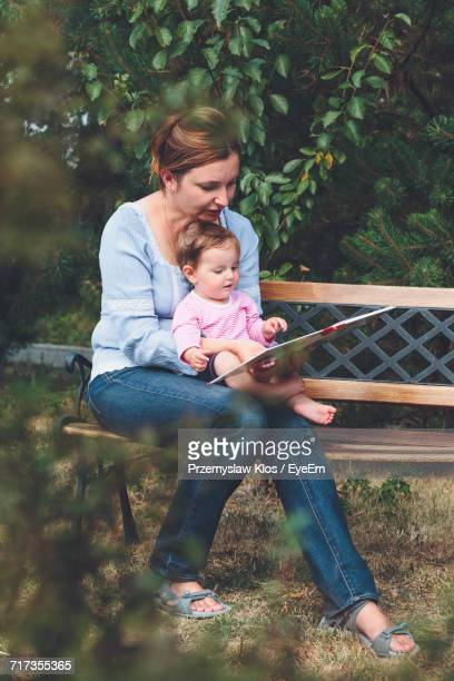 Mother Showing Book To Daughter While Sitting On Bench In Yard