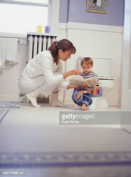 Mother showing book to son (15-18 months) sitting on potty