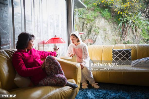 Mother showing cell phone to daughter wearing rabbit costume
