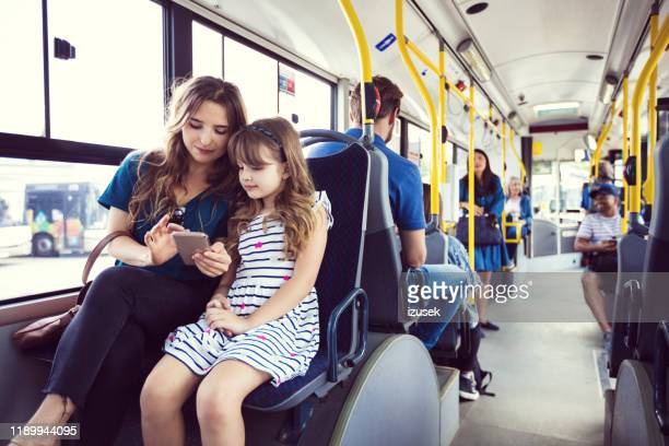 mother showing cellphone to daughter in bus - incidental people stock pictures, royalty-free photos & images