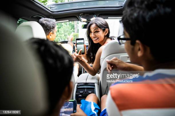 mother showing children vacation destination on smartphone - holiday stock pictures, royalty-free photos & images