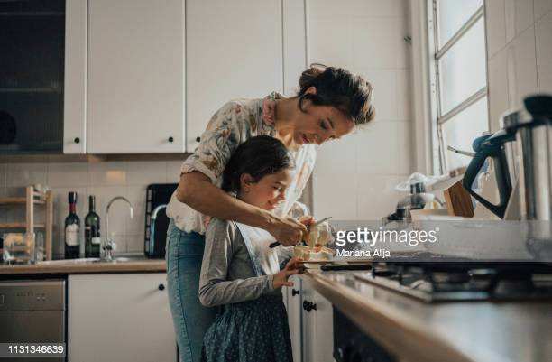 mother showing daughter how to peel an apple - real life stock pictures, royalty-free photos & images
