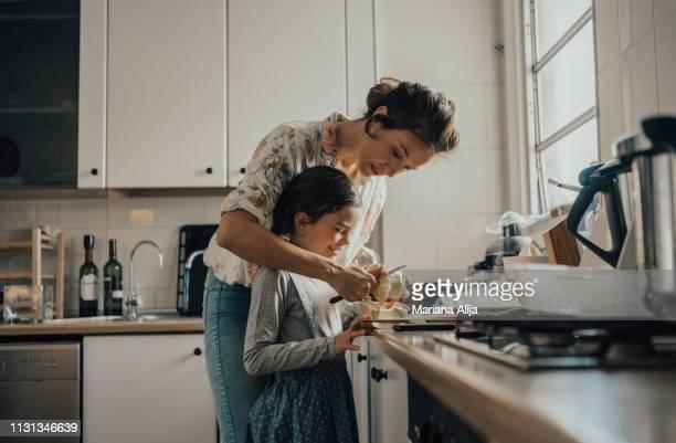 mother showing daughter how to peel an apple - cortar atividade - fotografias e filmes do acervo