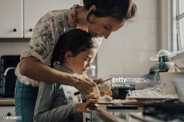 mother showing daughter how to peel an apple - europa meridionale foto e immagini stock