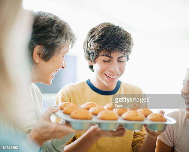 Mother Showing Fresh Cupcakes to Teenage Boy