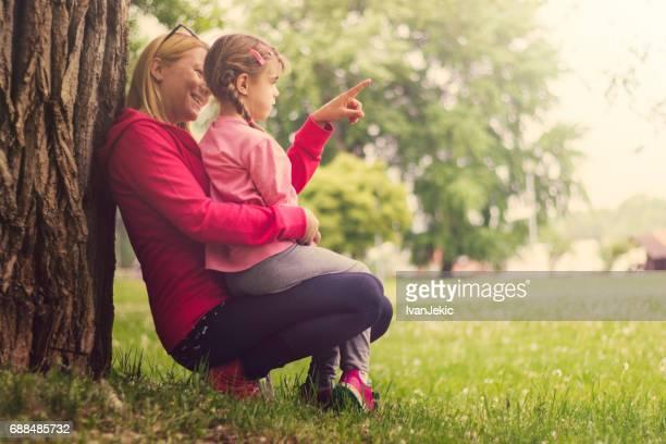 Mutter zeigt ihrer Tochter Bäume im park