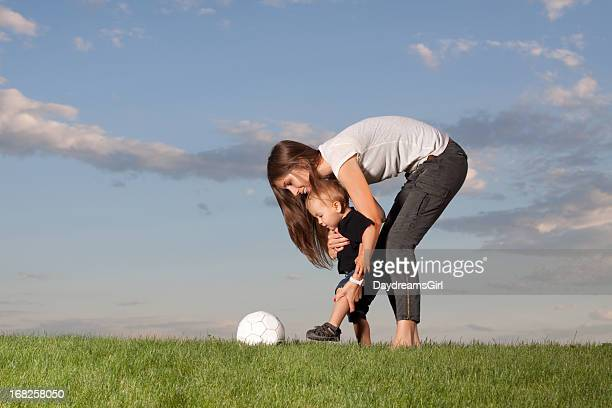 Mother showing her son how to kick a ball