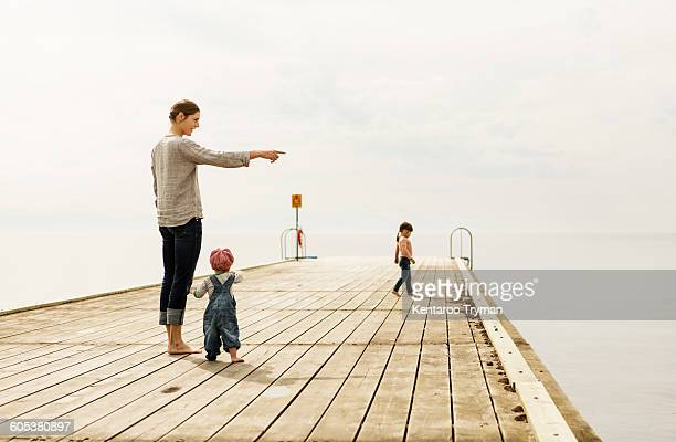 Mother showing something to baby girl while standing on pier at sea against sky