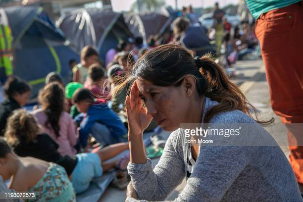 A mother sits as children take part in class at The Sidewalk School for immigrant children at a camp for asylum seekers on December 08 2019 in the...