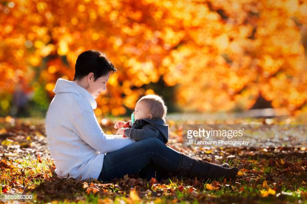 Mother Sits on Grass Looking at Child's Face while sitting on the leaves during beautiful fall day