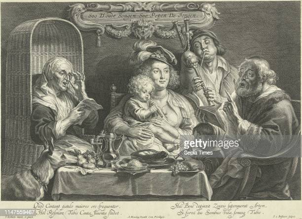 A mother sits with a small child playing flute on her lap on a set table besides her blowing her husband with chubby cheeks on a bagpipe and a little...