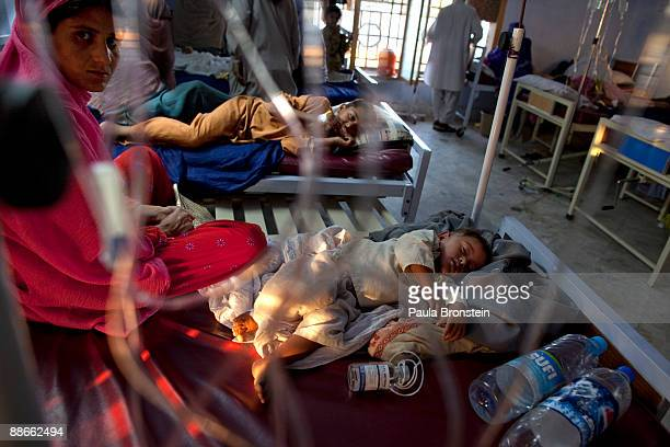 A mother sits with her baby hospitalized for stomach ailments diarrhea and dehydration at the Mardan District hospital special ward for the IDP's on...