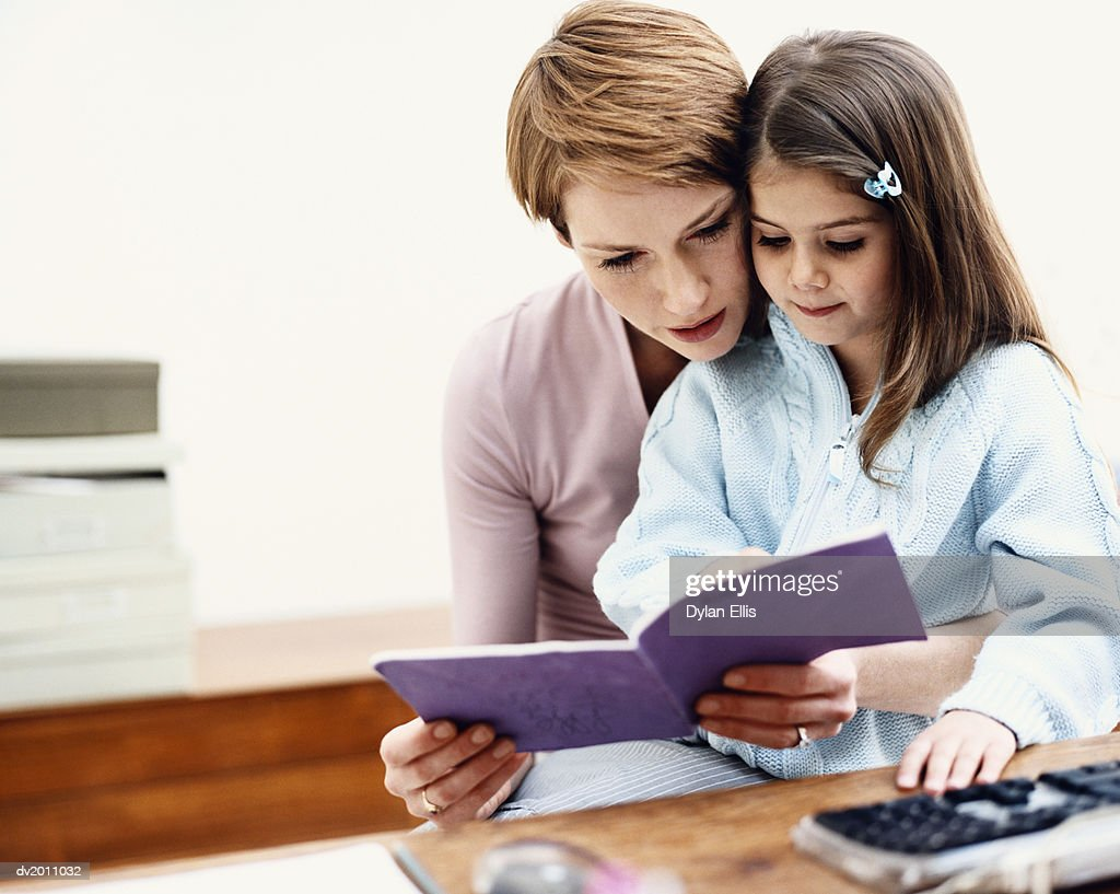 Mother Sits With Her Young Daughter, Reading to Her From a Book : Stock Photo