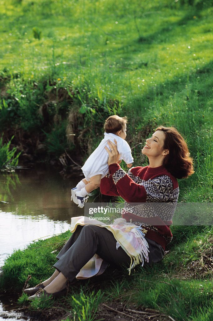 Mother sitting at lake's edge holding up baby : Stockfoto