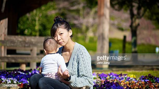 Mother sitting by a flower bed with baby daughter
