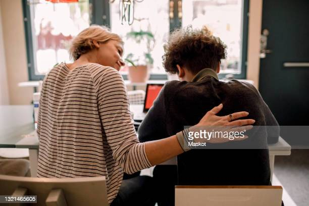 mother sitting by teenage son studying at home - back stock pictures, royalty-free photos & images