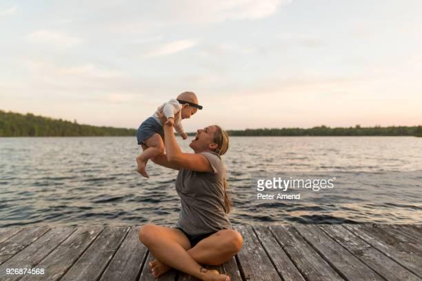 Mother sitting cross legged on lake pier holding up baby daughter