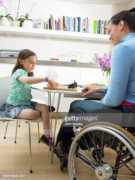 Mother sitting in wheelchair playing chess with daughter (6-8) at table