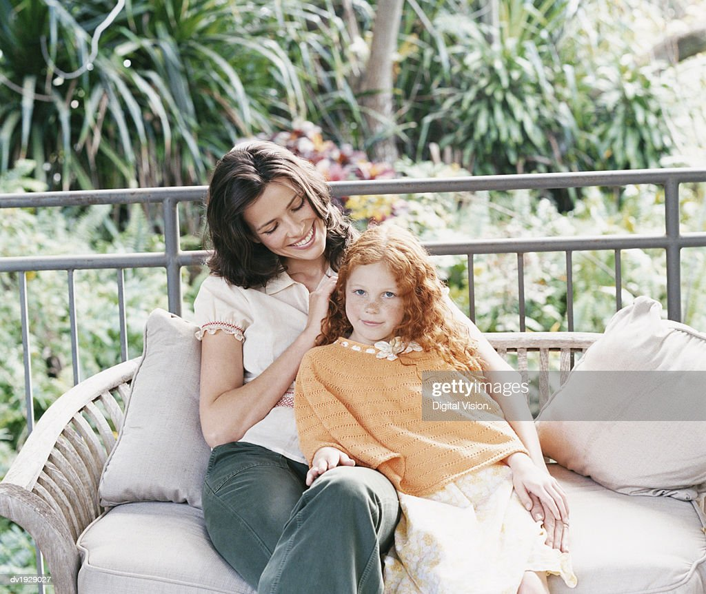 Mother Sitting on a Bench on a Patio With Her Daughter : Stock Photo