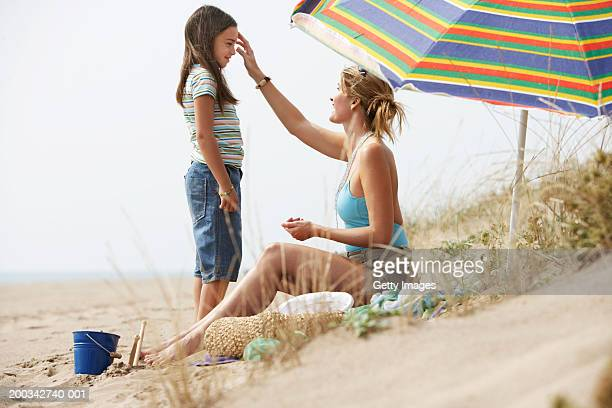Mother sitting on beach putting sun cream on daughter (8-10)