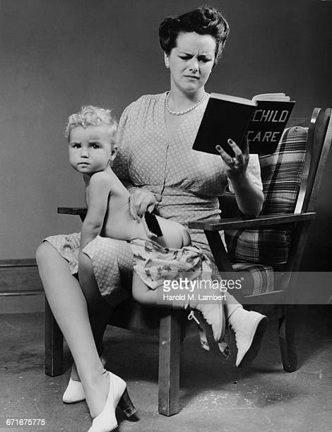 Mother Sitting On Chair Reading Child Care Book With Her Son On Lap