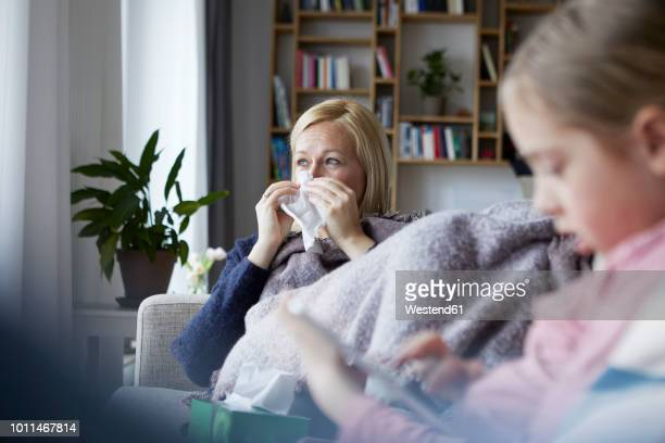 Mother sitting on couch, having a cold, daughter playing in foreground
