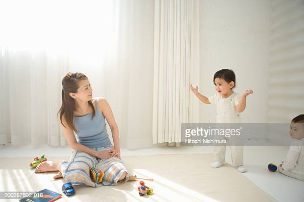 Mother sitting on floor looking over at children (6-21 months)