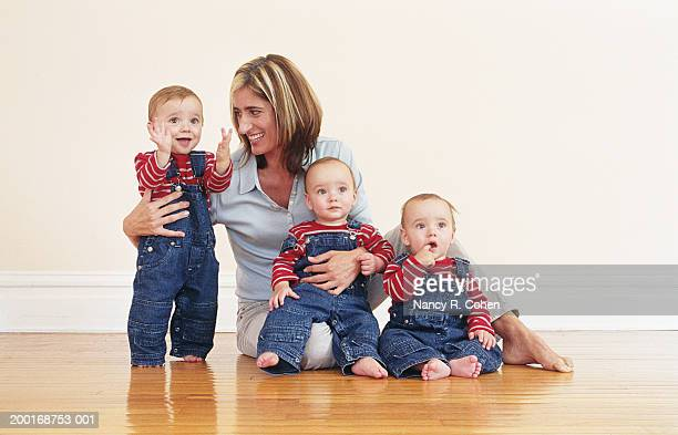 Mother sitting on hardwood floor with triplet baby boys (9-12 months)