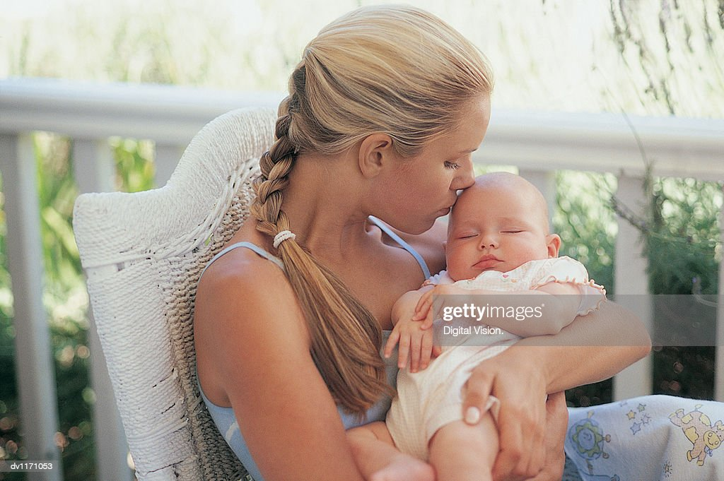 Mother Sitting on Her Porch Kissing Her Sleeping Newborn Baby : Stock Photo
