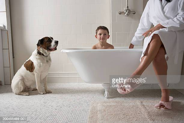 Mother sitting on side of tub with son (6-8) in bath tub and with dog