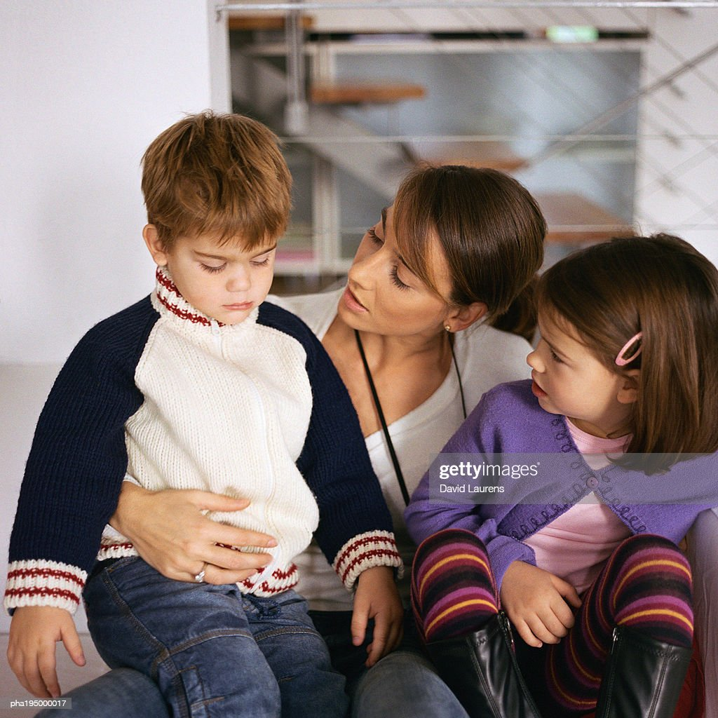 Mother sitting with children, looking at son. : Stock Photo