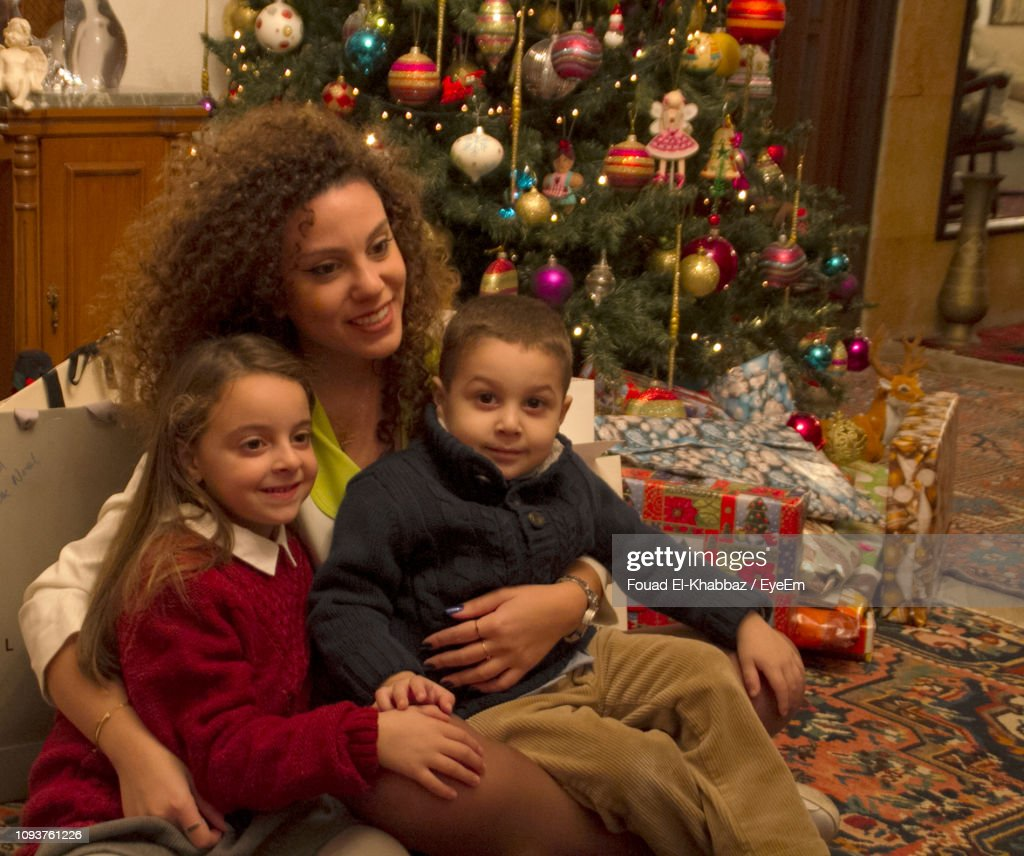Mother Sitting With Children On Chair At Home During Christmas : Stock-Foto