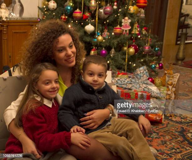 Mother Sitting With Children On Chair At Home During Christmas