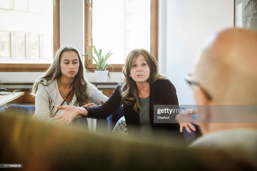 Mother sitting with daughter while sharing problems to male therapist at community center : ストックフォト