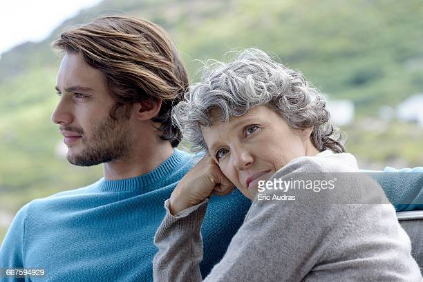 Mother sitting with her adult son outdoors