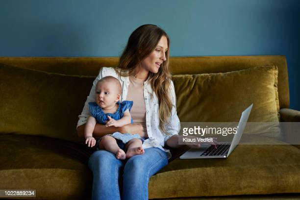 mother sitting with new born baby and laptop - multi tasking stock pictures, royalty-free photos & images