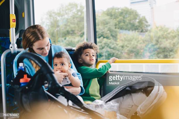Mother sitting with sons in bus