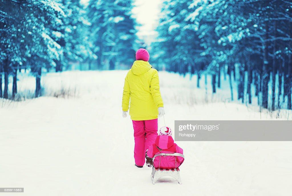 Trenó Puxado por mãe criança na floresta de Inverno NevadasComment : Foto de stock