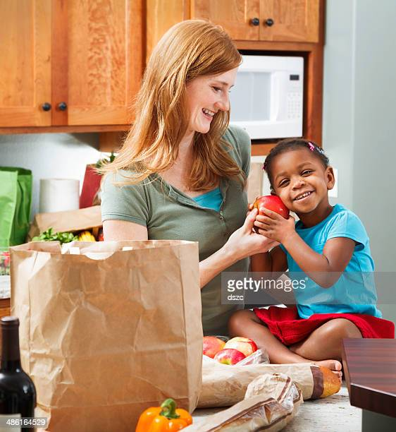 mother smiling at adopted daughter in kitchen with groceries