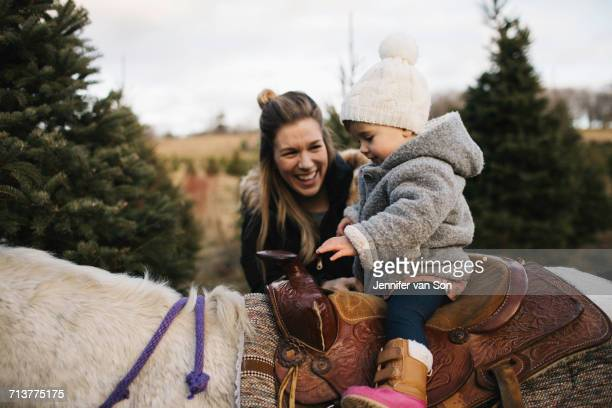 Mother smiling at baby girl riding on horse