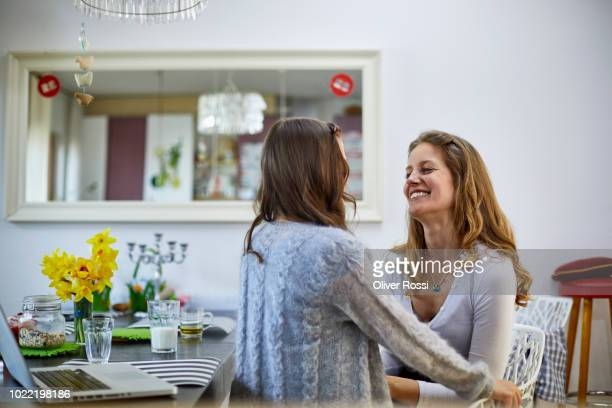 Mother smiling at daughter with laptop on dining table
