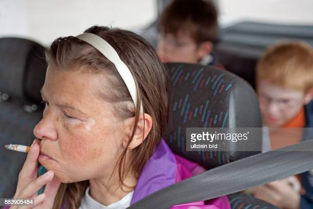 mother smoking while driving with her small sons in the back of her car / families / people / children / kids / smoking