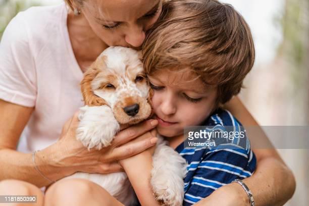 mother snd son cuddling with cute dog puppy - un animal fotografías e imágenes de stock