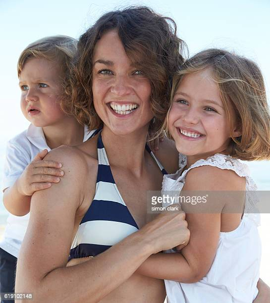 mother son and daughter embrace on beach