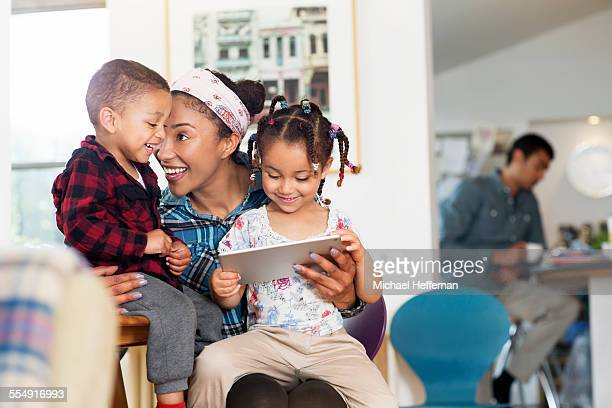 mother, son and daughter having fun with tablet - four people stock pictures, royalty-free photos & images