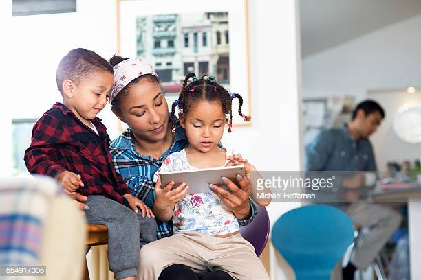 Mother, son and daughter looking at tablet device